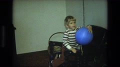1975: a small boy plays with a blue ball on a string inside his living room Stock Footage