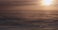 Orange sunset light on blowing snow over bleak tundra Stock Footage