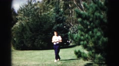 1962: boy wearing a t shirt is walking in the grass through a field or yard  Stock Footage