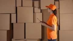 Female warehouse worker in orange uniform counting boxes and making records Stock Footage