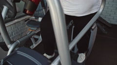 Chubby Woman Using Elliptical Trainer Stock Footage