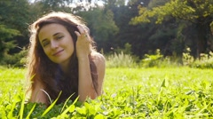 Happy caucasian girl enjoying sun and nature laying on grass, slow motion. Stock Footage