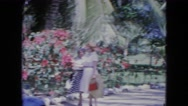 1964: pair of women on promenade chat and wave among the flowers and trees  Stock Footage