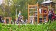 Children and parents having fun on playground in park, slow motion. Stock Footage