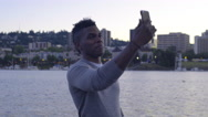 Man Stands On A Dock And Takes Selfies, Beautiful View Of City In Background Stock Footage