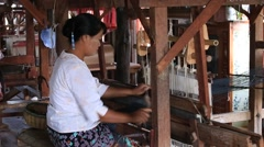 Women work on wooden weaving loom machines in textile manufacture, Burma Stock Footage