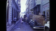 1964: men and woman walking past stacks of boxes in a truck on a city street Stock Footage