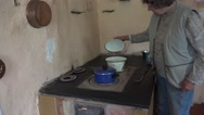Senior woman cook in pots on old furnace stove in rural kitchen. 4K Stock Footage