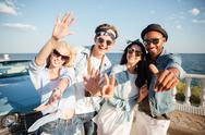 Multiethnic group of cheerful young people standing on promenade Stock Photos