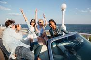 Group of cheerful people driving and having fun in cabriolet Stock Photos