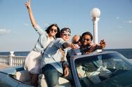 Happy young people driving car near the sea Stock Photos