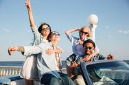 Cheerful young friends sitting and relaxing in car Stock Photos