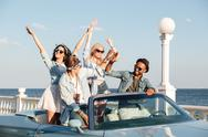 Joyful young people giving high five and driving cabriolet Stock Photos
