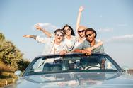 Group of happy young people in cabriolet Stock Photos