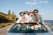 Cheerful young friends driving car in summer Stock Photos