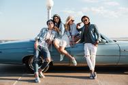 Cheerful young friends standing near the car Stock Photos