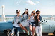 Smiling friends standing and sending kiss near cabriolet Stock Photos