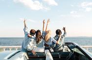 Back view of friends standing with raised hands near car Stock Photos