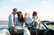 Back view of two couples embracing near cabriolet Stock Photos