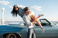 Man carrying his woman and having fun near vintage cabriolet Stock Photos