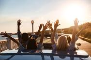 Back view of happy friends driving cabriolet with raised hands Stock Photos
