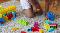 Little girl playing with plastic colorful bricks at home Stock Footage