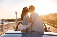 Couple sitting and kissing in car on sunset Stock Photos