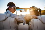 Beautiful young couple sitting in cabriolet in summer Stock Photos