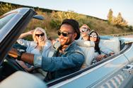 Cheerful young friends driving car and smiling in summer Stock Photos