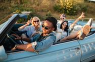 Smiling friends driving car and showing peace sign in summer Stock Photos