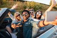 Happy young people taking selfie with smartphone in the car Stock Photos