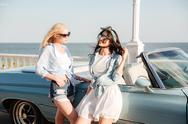Two women standing near cabriolet in summer Stock Photos