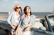 Two happy young women standing and waiting near cabriolet Stock Photos