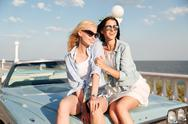 Two happy young woman sitting together on cabriolet Stock Photos