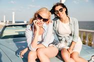 Two women sitting on the car hood together Stock Photos