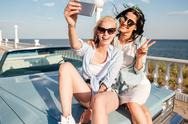 Two cheerful young women sitting on car and taking selfie Stock Photos