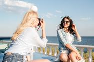 Cheerful woman sitting and posing to girl photographer in summer Stock Photos