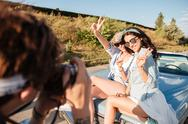 Two women showing peace sign and posing to man photographer Stock Photos