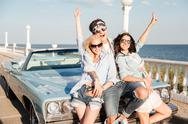 Cheerful young man and two women standing with raised hands Stock Photos