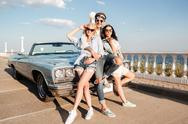 Cheerful man and two happy women standing near vintage cabriolet Stock Photos