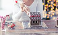 Close up of woman making gingerbread house at home Stock Photos