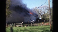 1968: fire department fights hard to put out the fire of the burning farm house. Stock Footage
