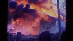 1968: two men outside in the street watching firemen extinguish a blazing fire Stock Footage
