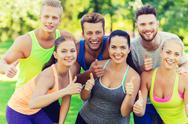 Group of happy sporty friends showing thumbs up Stock Photos