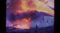 1968: large building engulfed in flames is being attended to by firefighters Stock Footage