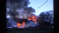 1968: firemen attempt to put out a large house fire with a water hose. WAUCONDA Stock Footage