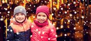 Little girl hugging boy over snow and carousel Stock Photos