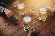 Close up of hands with beer mugs at bar or pub Stock Photos