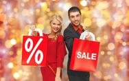 Couple with sale sign on shopping bags Stock Photos