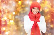 Happy woman in hat, scarf and mittens over lights Stock Photos